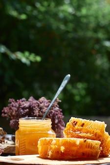 緑の葉に対する蜂蜜のガラス瓶、健康的な朝食のコンセプト