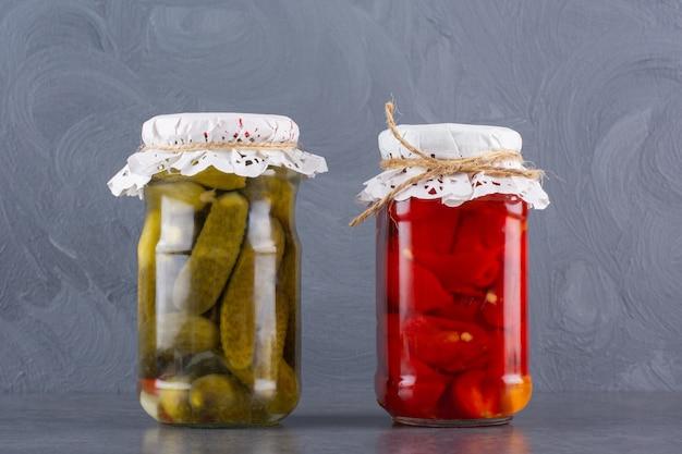 きゅうりとトマトのピクルスのガラス瓶を石のテーブルに。