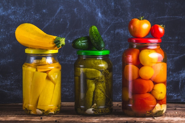 Glass jars of pickled homemade, fresh zucchini, cucumber and tomatoes on a dark background.