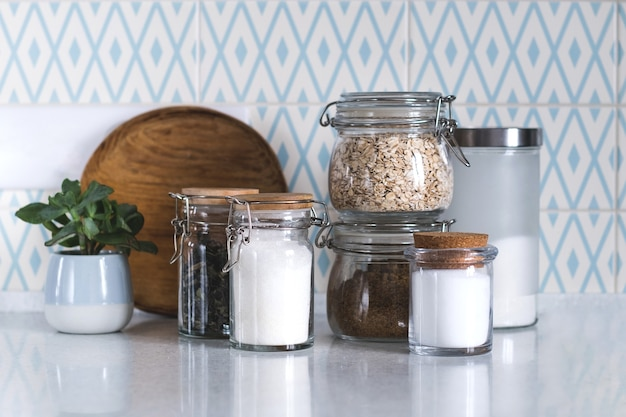 Glass jars of salt and cereals in the kitchen counter top.