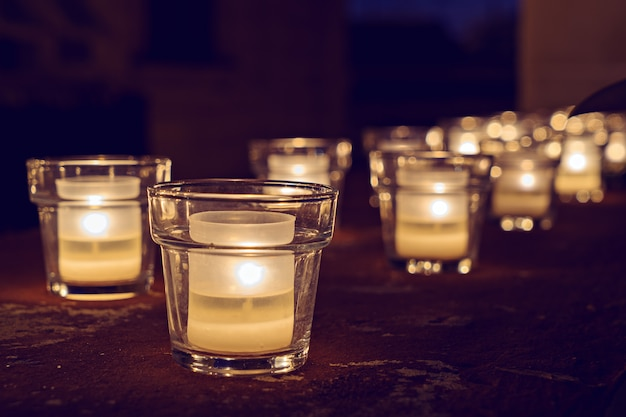 Glass jars with burning candles on the dark