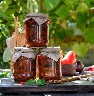Glass jars with canned aubergines in vegetable sauce