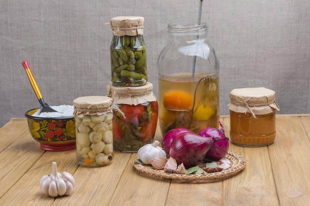 통조림 야채와 유리 항아리 테이블에 향신료 소금 마늘 양파 베이 리프 건강한 겨울 영양