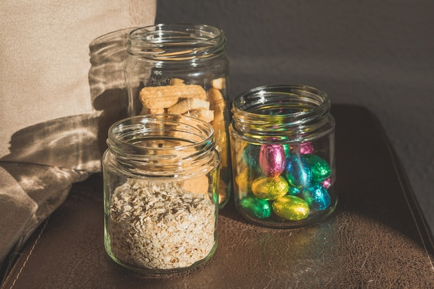 Glass jars with chocolate candies, oatmeal, honey, cookies and chocolates