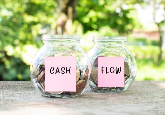 동전과 cash 및 flow가 새겨진 유리 항아리가 나무 테이블에 서 있습니다. 투자 예산.