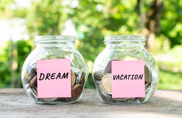나무 탁자 위에 동전과 dream 및 vacation이라는 글자가 새겨진 유리병이 있습니다. 투자 예산.