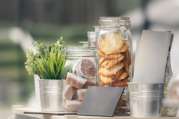 Glass jars with cookies and muffins, green seedlings in metal decorative pails.