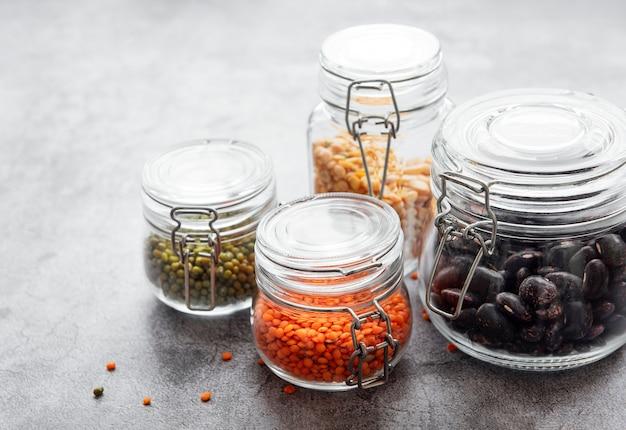 회색 콘크리트 책상에 다양한 종류의 콩과 식물이 담긴 유리 병