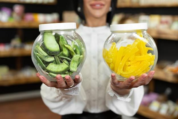 女性のセールスウーマンの手にドライフルーツと砂糖漬けの果物が入ったガラスの瓶