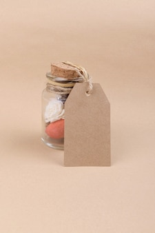 A glass jars with dried herbs for aromatherapy with empty rectungolar tag on craft paper backrgound