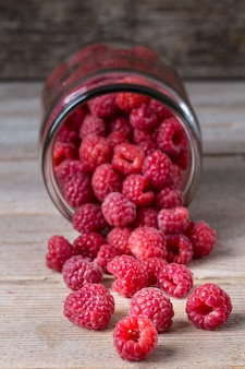 Glass jars with fresh ripe raspberries on table