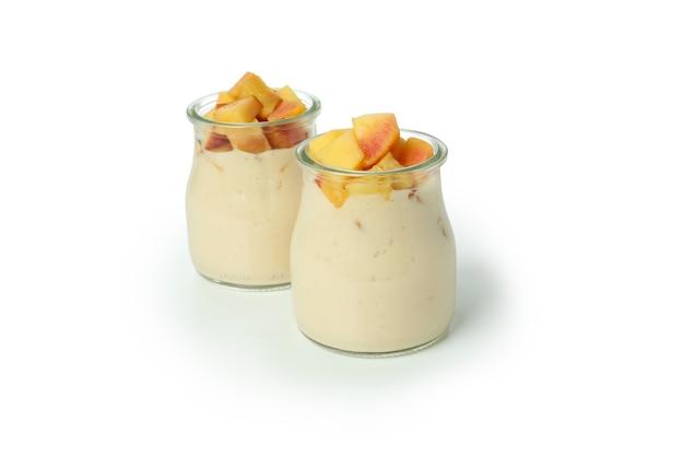 Стеклянные банки с персиковым йогуртом, изолированные на белом фоне