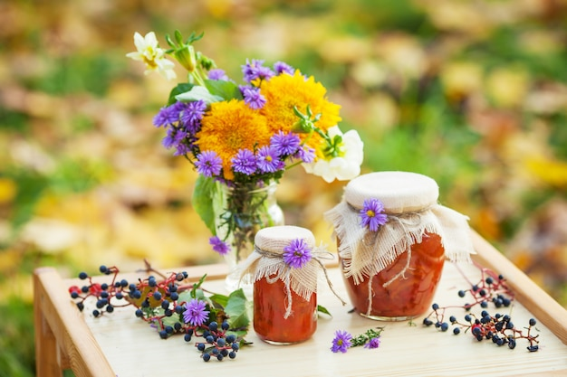 Glass jars with tasty apricot jam and bouquet of autumn flowers on a table. autumn time