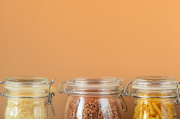 Glass jars with uncooked cereals, pasta, rice, buckwheat on a beige background.