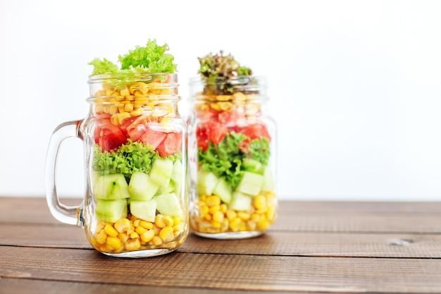 Glass jars with vegetable salad.