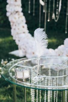 흰 꽃 아치에 유리 구슬로 장식 된 유리 테이블에 쓰기위한 펜 옆에있는 유리 보석 상자