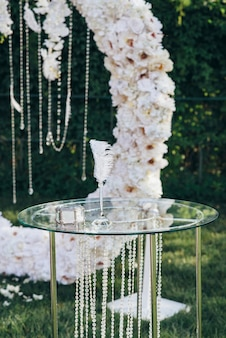 Glass jewelry box next to a pen for writing on a glass table decorated with glass beads against a white flower arch