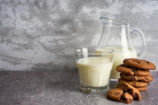 コピースペースと灰色の背景にミルクとチョコレートクッキーとガラスの水差しとガラス。