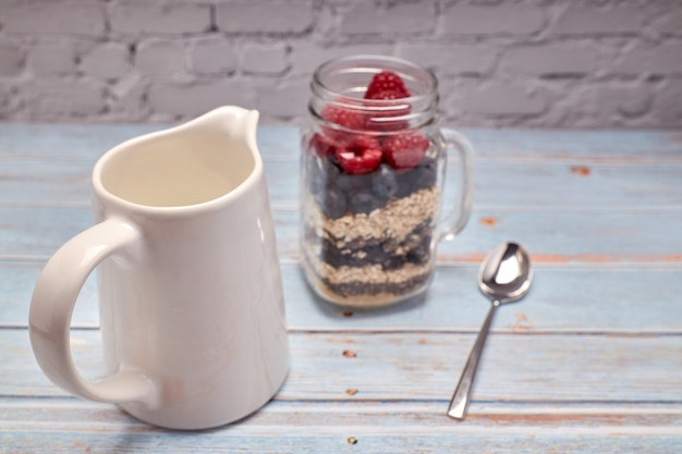 Glass jug filled with cereals, raspberries and blueberries