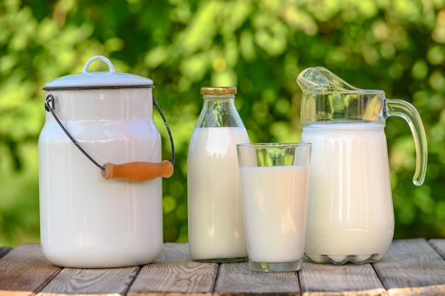 Glass and jug of fresh milk on wooden table