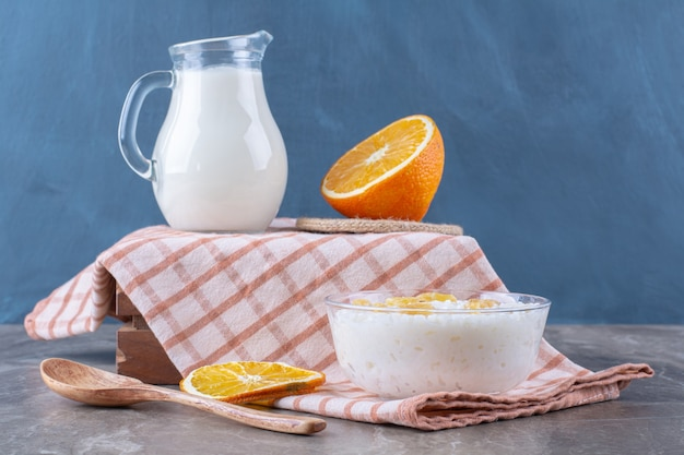 A glass jug of milk with healthy oatmeal porridge and sliced orange fruit .