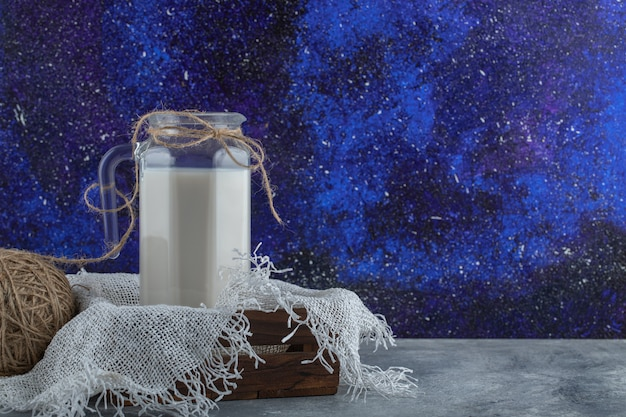 Glass jug of milk in wooden box with yarn.