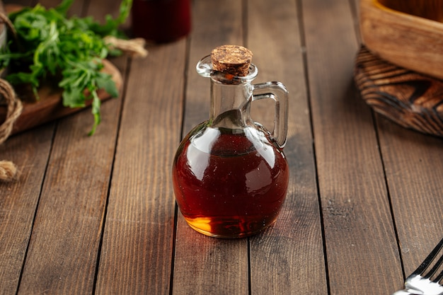 Стеклянный кувшин с кунжутным маслом на деревянных фоне