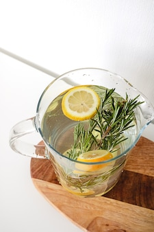 A glass jug of water with lemon and rosemary on a wooden cutting board on a white background
