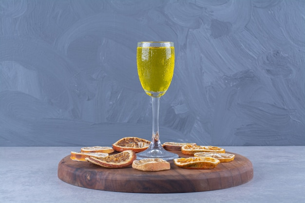A glass of juice, dried orange and lemon slices on board on marble table.