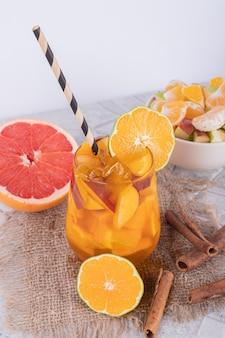 Un bicchiere di succo di frutta, fruttiera e cannella sulla parete di marmo.