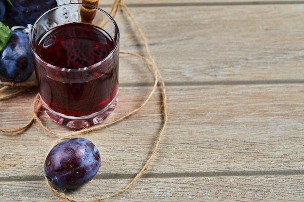 Un bicchiere di succo e prugne da giardino su un tavolo di legno.