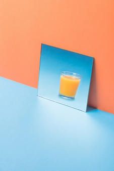 Glass of juice in mirror on blue table isolated