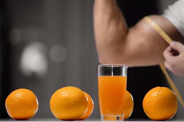 Glass of juice and oranges close-up on the of a man who measures his bicep with a measuring tape