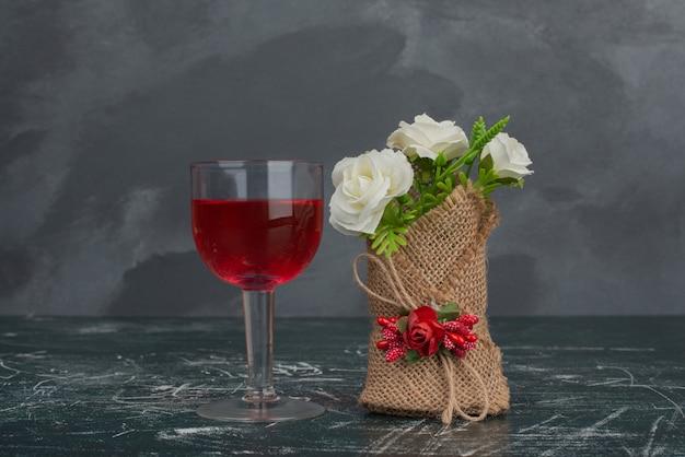 Bicchiere di succo e minuscolo bouquet sulla parete di marmo.