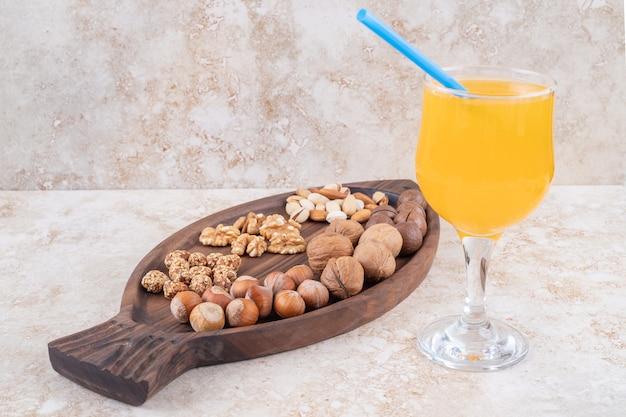 Un bicchiere di succo accanto a un vassoio con noci assortite e palline di cioccolato