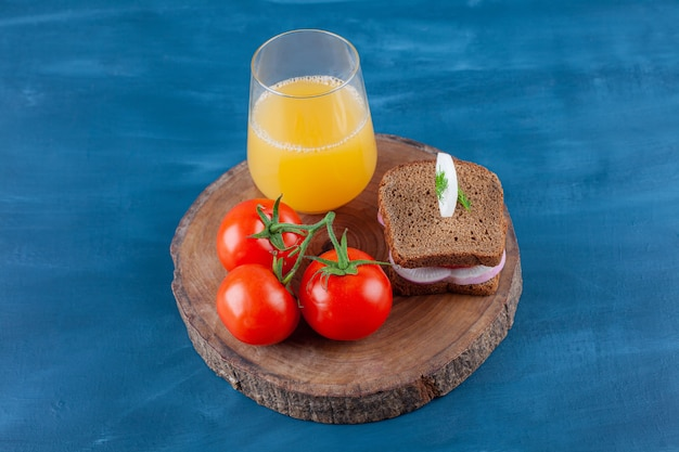 A glass of juice whole tomatoes and sandwich on a board , on the blue surface.