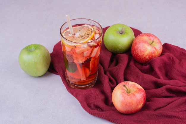 A glass of juice with apples on red towel
