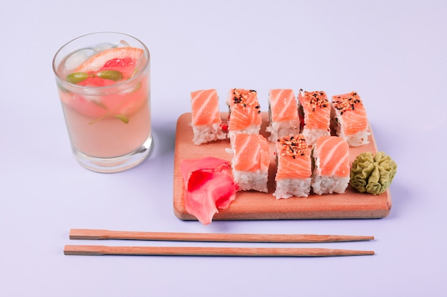 A glass of juice with classic salmon sushi; wasabi and pickled ginger on chopping board with chopsticks against white backdrop