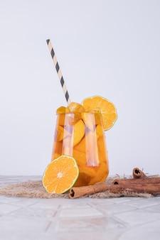 Un bicchiere di succo con fette di frutta e cannella sul muro bianco.