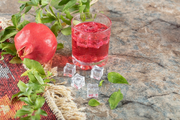 Glass of juice with ice cubes and pomegranate on stone surface