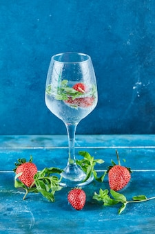 A glass of juice with strawberries and mint inside on blue surface