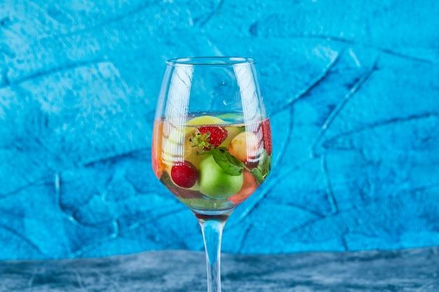 Un bicchiere di succo con frutti interi all'interno sulla superficie blu