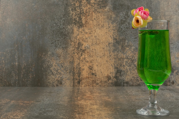 A glass of juicy green lemonade and roses on marble surface.