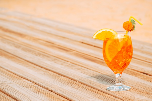 Glass of juicy orange drink on wooden table
