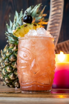 Glass of jungle bird cocktail garnished with pineapple wedge