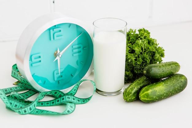Glass of kefir and clock