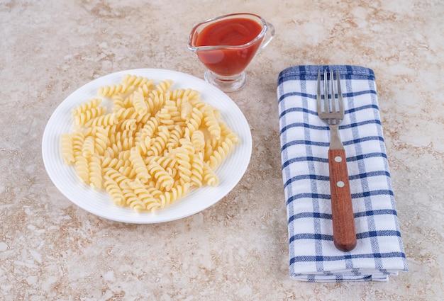 Bicchiere di ketchup, condimento per la cena con maccheroni e forchetta su un asciugamano su una superficie di marmo