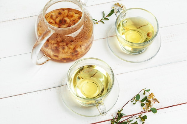 Glass kettle and cup of herbal tea on white wooden background