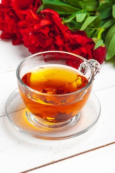 Glass kettle of herbal tea with fresh flowers close up