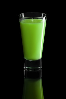 Glass of kiwi and celery cocktail isolated on black